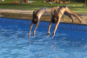 Two girls are thrown into a pool — Stock Photo