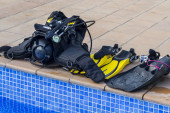 Scuba diving equipment on the edge of a pool — Stock Photo