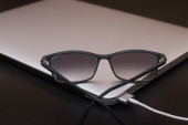 Glasses on the charging silver laptop — Stock Photo