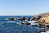 Rocky cliff on pacific ocean ocean shore in northern California next to Big Sur state park with waves and rocks — ストック写真