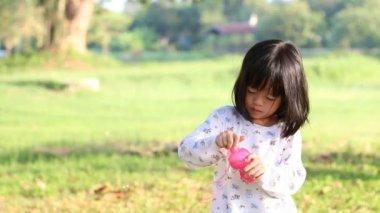 Cute little girl blowing a soap bubbles, Green garden background. — Stock Video