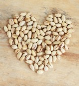 Pistachio nuts in heart shape — Stock Photo