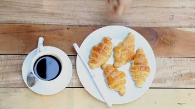 Overhead view of a woman hand with a cup of black coffee and a freshly baked croissant. — Stock Video