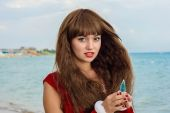 Happy and beautiful girl Santa Claus on the beach. — Stock Photo
