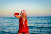 Beautiful girl Santa Claus on the beach — 图库照片