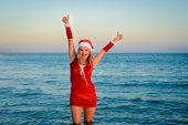 Beautiful girl Santa Claus on the beach — Stock Photo