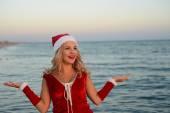 Beautiful girl Santa Claus on the beach — Stock Photo
