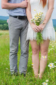 Beautiful couple in love on camomile field — Stockfoto