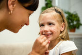 Woman paints the face of a child for the holiday — Stock Photo