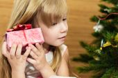 Girl with a gift in the Christmas tree. — Stock Photo