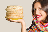 Portrait of a beautiful cheerful young woman with pancakes. — Stock Photo