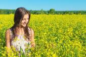 Portrait of a beautiful young woman among blossoming field — Stok fotoğraf