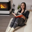 Beautiful woman reading book by fireplace — Stock Photo #78439624
