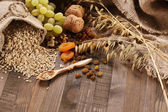 Oatmeal in a sac, ears of oats, dried apricots, raisins, grapes, — Stock Photo