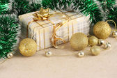 Gift, gold balls on the background cloth — Stock Photo