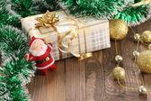 Gift, a garland of golden balls, Santa Claus  — Stock Photo