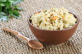 Rice with vegetables in a ceramic bowl on a mat  — Stock Photo