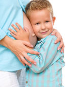 Happy child holding belly of pregnant woman — Stock Photo