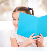 Little girl is playing with book — Stock Photo