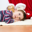 Cute boy daydreaming lying on the floor. New Year — Stock Photo #59468437