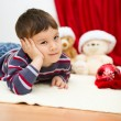 Cute boy daydreaming lying on the floor. New Year — Stock Photo #59468443
