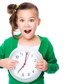 Cute girl is holding big clock — Stock Photo