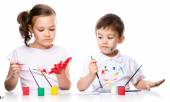 Cute boy and girl playing with paints — Stock Photo