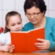 Grandmother is reading book with her granddaughter — Stock Photo #65472713