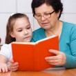 Grandmother is reading book with her granddaughter — Stock Photo #65472723