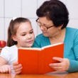 Grandmother is reading book with her granddaughter — Stock Photo #65472729