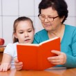 Grandmother is reading book with her granddaughter — Stock Photo #65472745