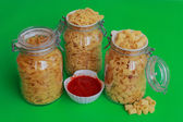 Three jars of pasta with red sauce bowl — Stock Photo