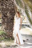 Beautiful woman on the beach in wedding dress — Stock Photo