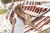 Beautiful young bride sitting on boat near the sea — Stock Photo