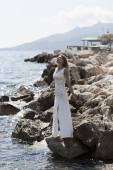Beautiful bride stands on a cliff above the sea in glamorous white wedding dress — Stock Photo