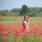 Beautiful Girl in the poppy field, red dress — Stockfoto