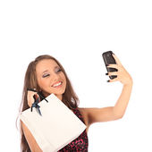 Beautiful girl holding shopping bags and taking selfie with cell phone — Foto de Stock