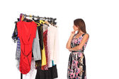 Which dress should I pick, young woman holding wear — Stockfoto