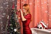 Beautiful woman decorating the Christmas tree — Stock Photo