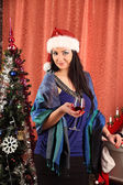 Winter, holidays, happiness and people concept - smiling woman in santa helper hat over living room with christmas tree background — Stock Photo