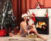 Christmas girl near the fireplace and tree — Photo
