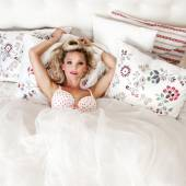 Romantic blonde woman posing in bed — Stock Photo