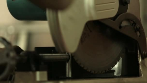 Circular saw cuts L shape steel rod. Previously measured before divided in two. Sparks observed in the process. — Vídeo de stock