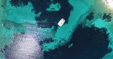 Aerial, top drone scene of catamaran anchored in a bay with transparent turquoise water and patterned shore. — Stock Video