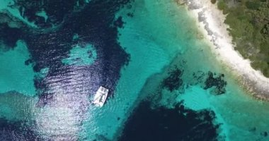 Aerial, top scene of transparent doted shore of a virgin island. Catamaran anchored. — Stock Video