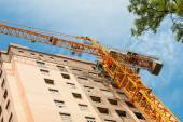 Jeřáb a budování staveniště proti modré obloze — Stock fotografie