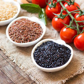 Variety of rice in bowls and tomatoes on wooden table — Stock Photo