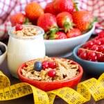 Jars of fresh yogurt, berries, muesli and measuring tape  — Stock Photo #54027707
