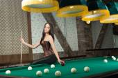 Sexy girl in corset plays billiards. — Stock Photo
