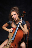 Beautiful female musician playing a cello. — Stock Photo